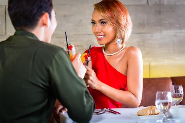 Азиатская пара пьет коктейли в модном баре
