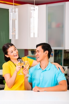 Asian couple drinking white wine at home