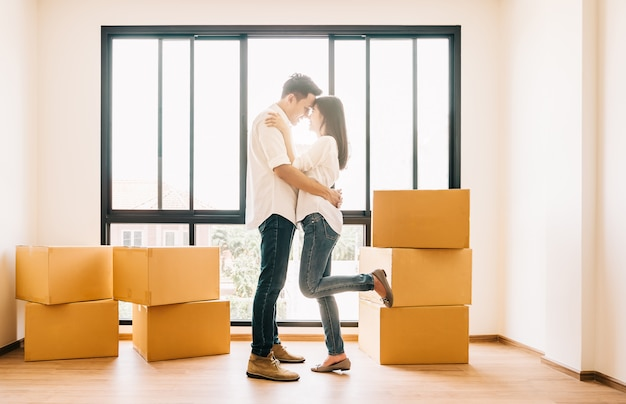 Asian couple embracing in their new home