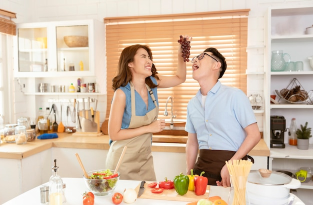 アジアのカップルは、自宅のキッチンルームで一緒にサラダを調理するのを楽しんでいます。