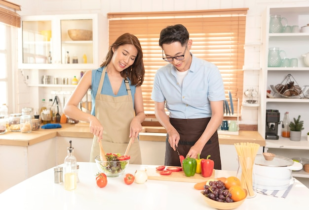 Asian couple enjoy cooking salad together in kitchen room at home.