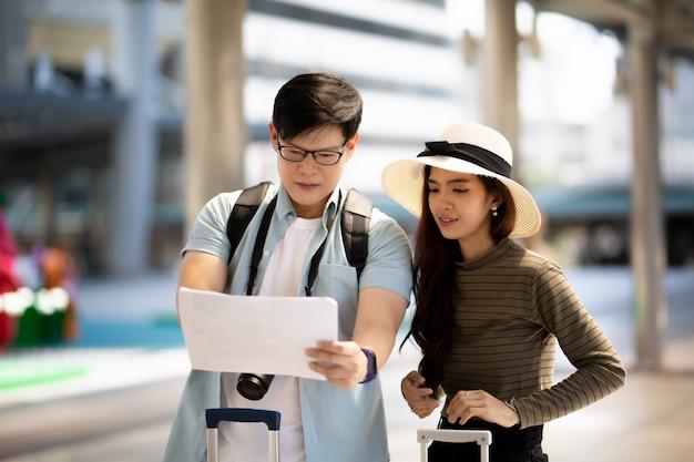 アジアのカップルは、街の街を旅したり歩いたりするのを楽しんでいます。