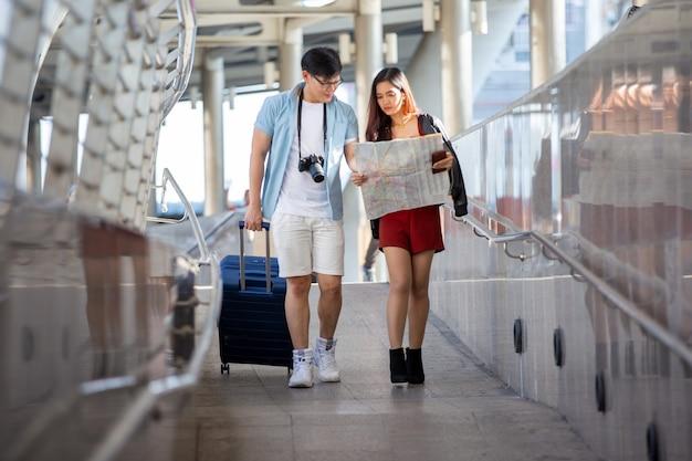 Азиатская пара любит путешествовать и гулять по улице в городе.