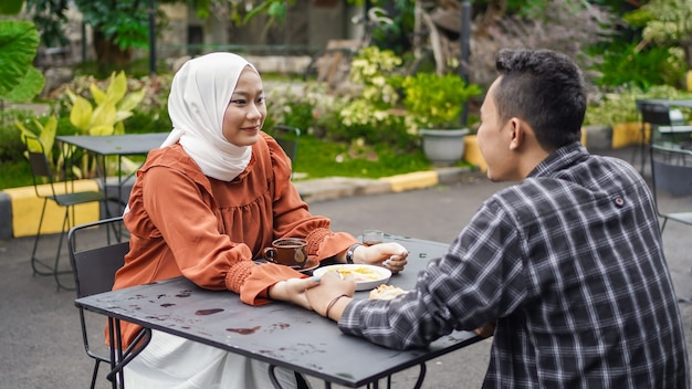 Asian couple happy dating holding hands at cafe