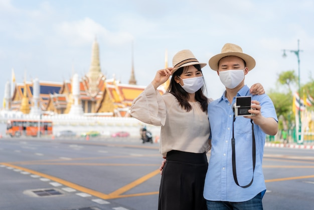Asian couple happy tourists to travel wearing mask