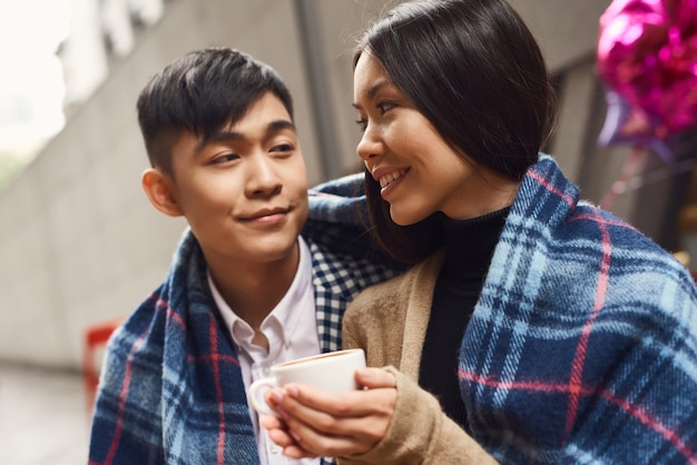 Asian couple has latte in coffee shop outdoor.