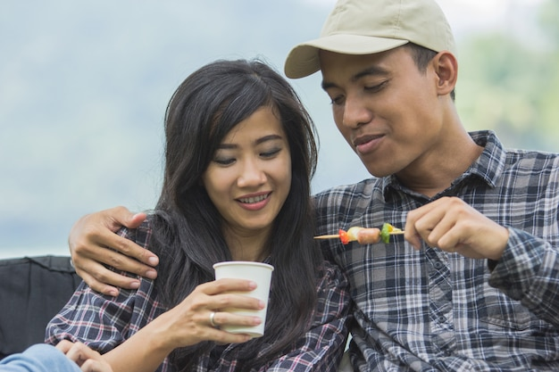 Asian couple having barbecue skewers