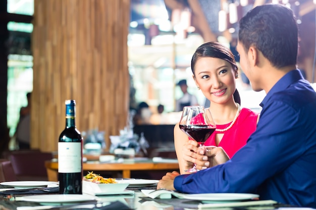 Asian couple having dinner and drinking red wine in very fancy restaurant with open kitchen