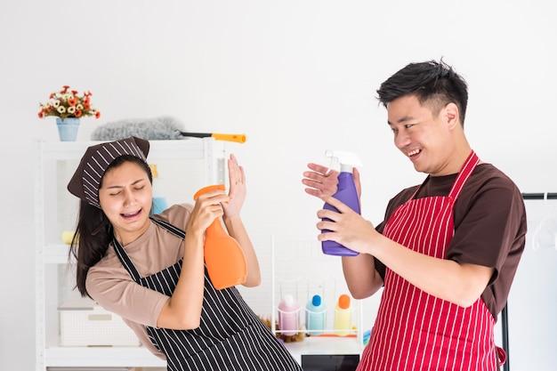 Азиатская пара весело распыляет воду во время уборки дома