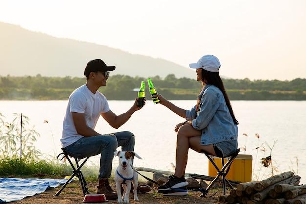 야외에서 캠핑 텐트를 마친 후 환호와 음료를 위해 알코올 맥주 병을 들고 있는 아시아 커플. 태국 사람들은 야외에서 재미있고 쾌활합니다.