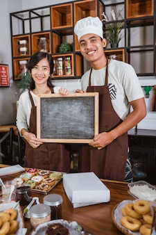 Asian couple holding a blackboard while standing in the kitchen