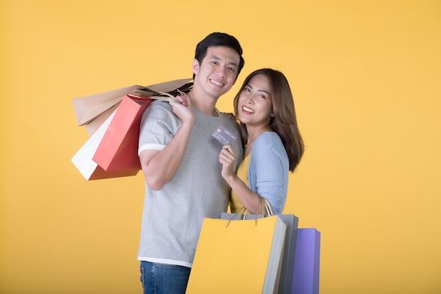 노란색 배경에 격리된 신용카드와 쇼핑백을 들고 있는 아시아 커플