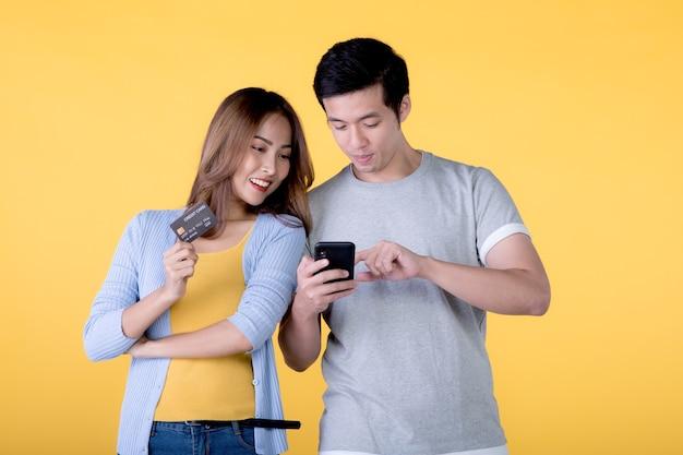 黄色の背景で隔離のクレジットカードとスマートフォンを保持しているアジアのカップル