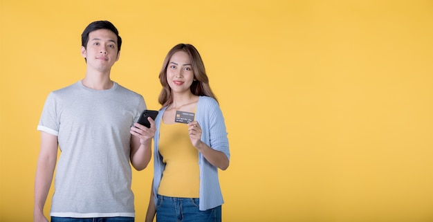 黄色の背景で隔離のカメラを見ながらクレジットカードとスマートフォンを保持しているアジアのカップル