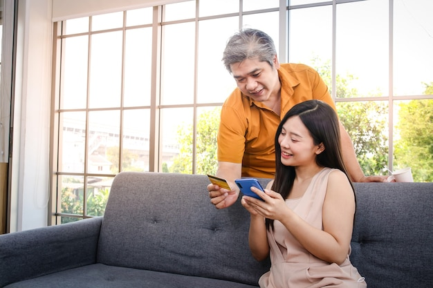 Asian couple holding credit card and smartphone to order online instead of going out of the house. self-defense, stay at home during the coronavirus spread. social distance