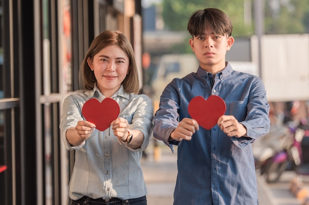 Asian couple holding red heart