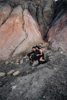Азиатская пара в любви обнимает, сидя на скалах. любовная история