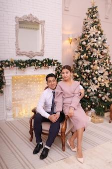 エレガントな衣装で恋をしているアジアのカップルは、豪華な家の暖炉と木のそばでクリスマスを祝います
