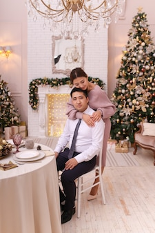 Азиатская влюбленная пара мужчина и женщина в элегантных нарядах обнимаются у камина и дерева