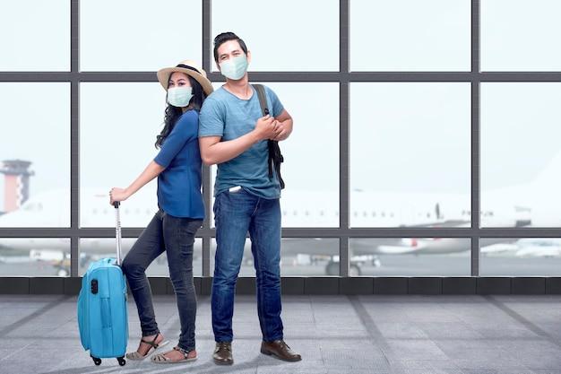 가방 가방과 배낭 공항 터미널에 서있는 얼굴 마스크에 아시아 부부. 새로운 노멀 여행