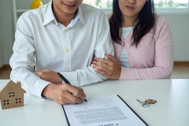 アジアのカップルが住宅ローンの契約または住宅を購入しています。夫婦は、販売員に相談した後、家を売買することに同意した。契約と署名の概念。