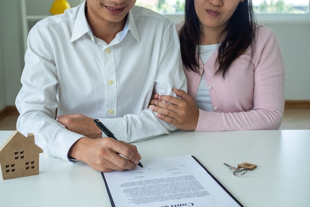 Asian couple is signing a mortgage contract or buying house. the husband and wife agreed to buy or sell the house after talking to a salesperson. the concept of a contract and sign.