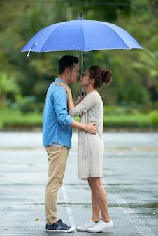 アジアのカップルが雨の中でキス