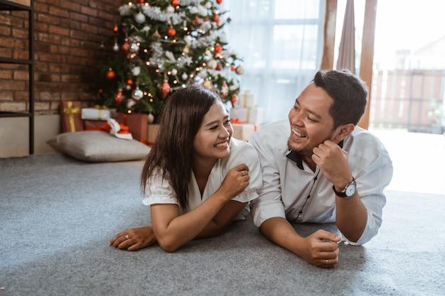 クリスマスツリーを背景に床に一緒に横たわっているアジアのカップル