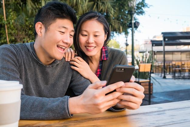 携帯電話を見てアジアカップル。