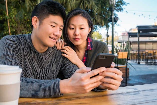 Asian couple looking at the mobile phone.