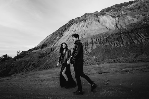 An asian couple in love in black leather clothes walk in nature among the trees. black-white