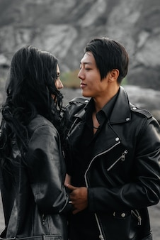An asian couple in love in black leather clothes walk in nature among the trees. style, fashion, love Premium Photo