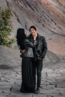 An asian couple in love in black leather clothes walk in nature among the trees. style, fashion, love.
