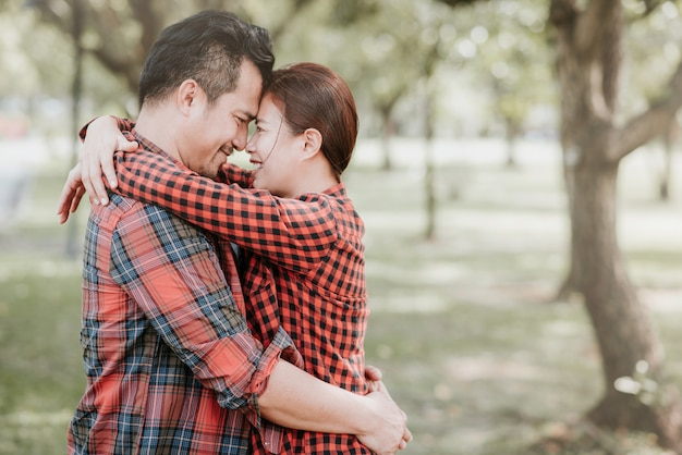 Asian couple in love embracing in the park