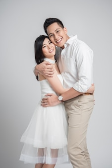 Asian couple in love embracing on white background