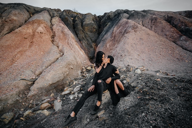 Asian couple in love hugs sitting on the rocks. love story.