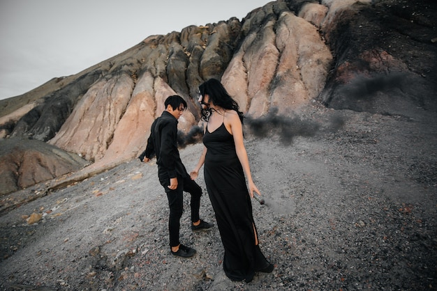 An asian couple in love lit black smoke bombs in the mountains. colored smoke