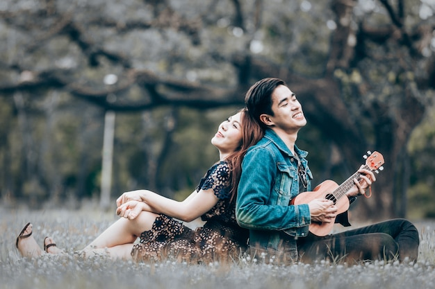 Asian couple in love playing acoustic ukulele song sitting on grass in the park