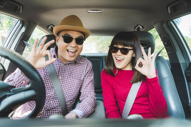 Asian couple love showing ok sign in car.