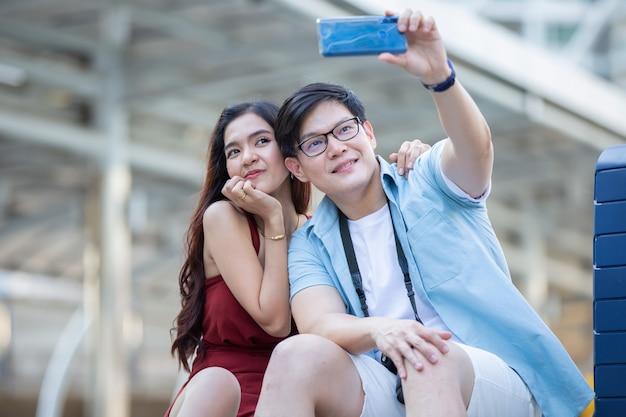 アジアのカップルの愛は通りで携帯電話で写真を撮る