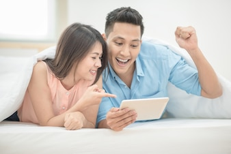 Asian couple lovers enjoy cheer up online esport on smart tablet on holiday vacation in bedroom.