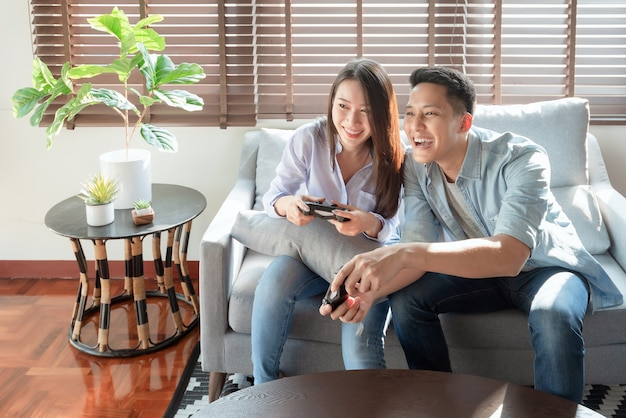 Asian couple lovers enjoy and play console game on vacation make more quality time of happiness together at home
