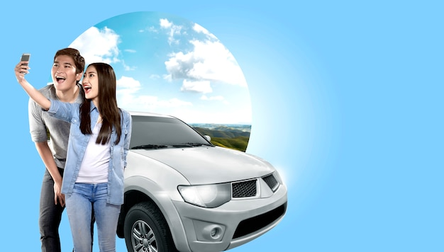 Asian couple making selfie on mobile phone camera posing beside automobile with green hills background