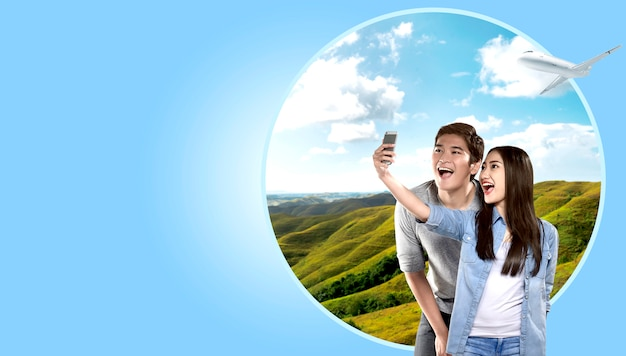 Asian couple making selfie on mobile phone camera with green hills background