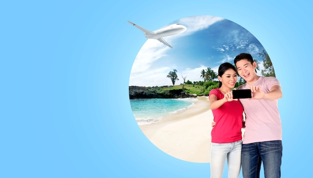 Asian couple making selfie on mobile phone camera with sandy beach background
