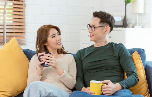 自宅のリビングルームのソファで一緒にコーヒーを飲むアジアのカップルの男性と女性。家族のライフスタイルの概念。