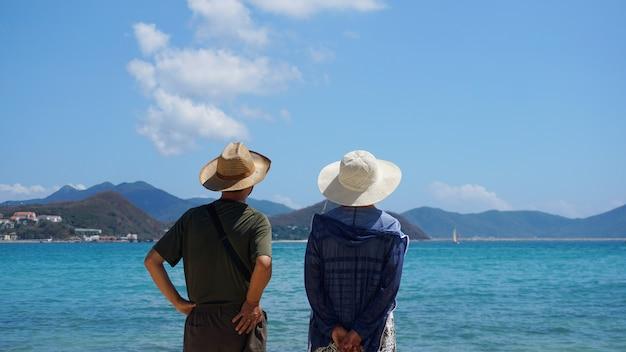 ビーチの海辺に滞在し、目をそらす帽子をかぶったアジアのカップルの男性と女性