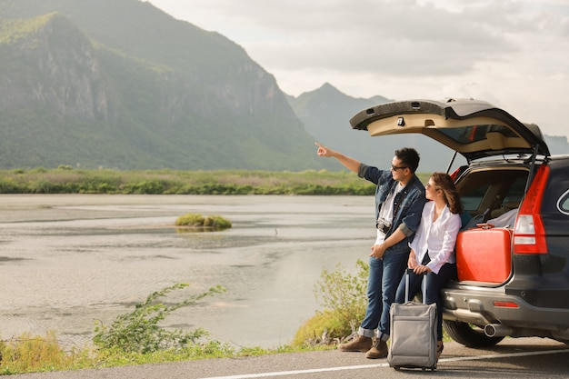 Asian couple man with vintage camera and woman sitting on back of car  travel to mountain and lake in holiday with car road trip