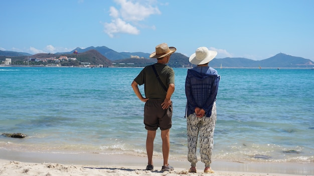 Asian couple man and woman in hats staying on beach seaside and look away