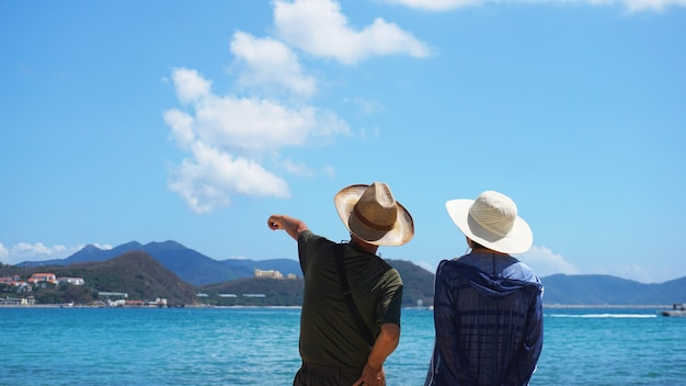 Asian couple man and woman in hats staying on beach seaside and look into the distance. a man indicates the direction of the hand.